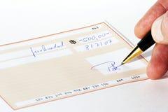 Inscription d'un chèque bancaire Photographie stock