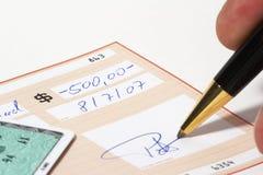 Inscription d'un chèque bancaire Photos libres de droits