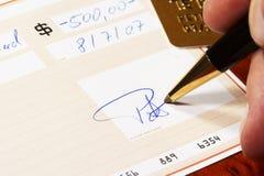 Inscription d'un chèque bancaire Images stock