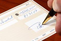 Inscription d'un chèque bancaire Photo stock