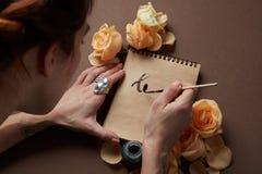 Inscription d'une lettre d'amour avec des roses Photos stock