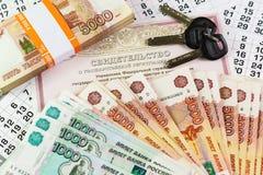 Inscription dans le Russe : Certificat de l'enregistrement d'état des immobiliers Documents et clés sur une grande somme d'argent photos stock