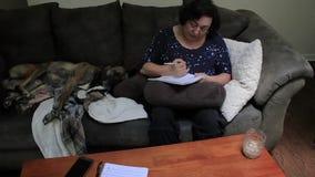 Inscription dans un bloc-notes à côté du chien banque de vidéos