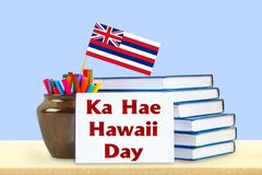 Inscription Day of the Hawaiian flag -31 July. A stack of books, markers and pens on a wooden table. royalty free stock photo