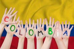 Inscription de la Colombie sur les mains des enfants dans la perspective d'un drapeau de ondulation de la Colombie illustration de vecteur