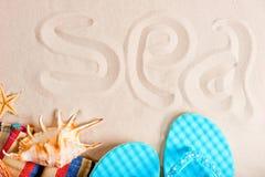 Inscription de mer sur les sables et l'attirail fins de plage Photos libres de droits