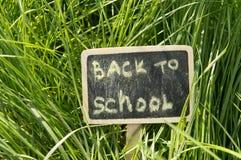 Inscription de nouveau à l'école écrite dans la craie sur un fond de tableau noir d'herbe verte Photographie stock libre de droits