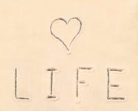 Inscription de vie amoureuse dessinée sur le sable Image stock