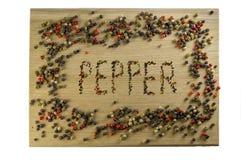 Inscription des poivrons sur une planche à découper, faite avec le poivre, dans un cadre de poivre image stock
