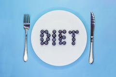 Inscription Diet made of blueberries on white plate with cutlery. Light blue background. Flat lay. Top view stock photo
