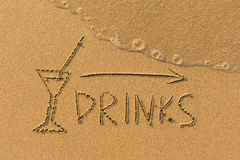 Inscription Drinks and the arrow drawn on the beach sand Royalty Free Stock Photo