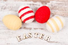 Inscription Easter and colorful eggs wrapped woolen string on rustic board Royalty Free Stock Images