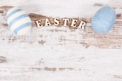 Inscription Easter and colorful eggs wrapped woolen string on rustic board, copy space for text Stock Photos