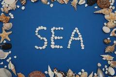 Inscription en pierre, texte, mot : MER au-dessus de fond bleu Cadre de coquilles Concept nautique et de Marinne Image libre de droits