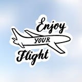 The inscription: `Enjoy your Flight`, with image airplane, drawn in black ink on a realistic blue sky. Royalty Free Stock Image