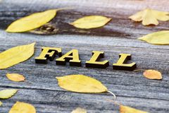 Inscription Fall on a wooden background, frame of yellow leaves.  Stock Photos