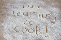 The inscription of flour I'm learning to cook. On a wooden board Royalty Free Stock Photo