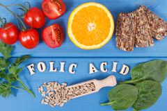 Inscription folic acid with healthy nutritious food as source minerals, vitamin B9 and dietary fiber royalty free stock photo