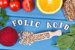 Inscription folic acid with healthy nutritious food as source minerals, vitamin B9 and dietary fiber royalty free stock image