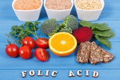 Inscription folic acid with nutritious different ingredients containing vitamin B9 and natural minerals, healthy nutrition concept stock images