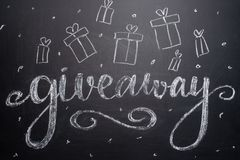 The inscription giveaway is written on a blackboard with gifts. Distribution of gifts. Blog, bloggers, social networks, instagram stock photos