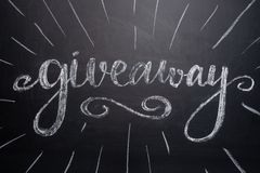 The inscription giveaway is written on a blackboard with gifts. Distribution of gifts. Blog, bloggers, social networks, instagram stock image