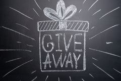 The inscription giveaway is written on a blackboard with gifts. Distribution of gifts. Blog, bloggers, social networks, instagram royalty free stock photos