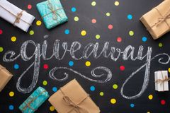 The inscription Giveaway is written on a blackboard with gifts. Free distribution, bloggers and gifts royalty free stock image