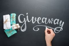 Inscription Giveaway written on the board with gifts stock photo