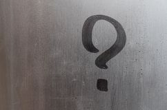 The inscription on glass, question mark concept. Question sign is painted on the surface of misted and wet window royalty free stock photo
