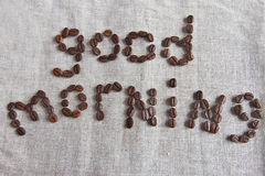 The inscription good morning of the coffee beans. At the tissue background Stock Images
