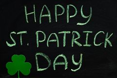 The inscription with green chalk on a chalkboard: Happy St. Patrick's Day. Clover leaves. Stock Image