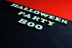 Inscription HALLOWEEN PARTY made of wooden letters on a black background. Red upper right corner of the frame. stock photography