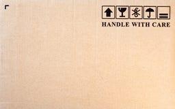 Fragile symbol on cardboard background. Inscription `handle with care` and fragile symbol on cardboard background stock photos