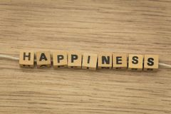 Inscription / happiness / arranged from blocks strung on a string. View of the inscription / happiness / arranged from blocks strung on a string Royalty Free Stock Images