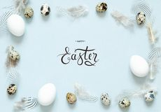 Inscription Happy Easter. Easter composition with easter eggs,  and feathers. Flat lay, top view royalty free stock photos