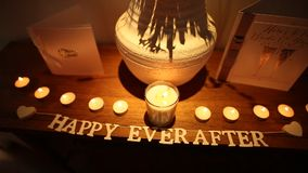 The inscription `Happy Ever After` on the table and the candles. The inscription Happy Ever After on the table and the candles. Wedding decorations. Wedding in stock video footage