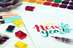 Inscription - happy New Year. Girl makes the inscription watercolor - happy New Year stock image