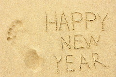 Inscription 'HAPPY NEW YEAR' and human footprint in the sand on Royalty Free Stock Photo