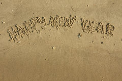 Inscription Happy new year on the sand Royalty Free Stock Photos