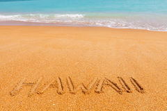Inscription Hawaii on the beach by the blue sea Stock Photography