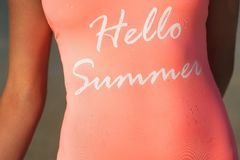 The inscription is hello summer on a pink swimsuit. Girl in pink bathing suit close-up with droplets stock image