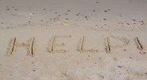 Inscription HELP!  on a sandy beach Royalty Free Stock Photo