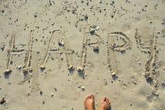 Inscription heureuse écrite sur la plage blanche de sable Jour de vacances ensoleillé de bord de la mer Images stock