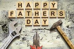 Inscription heureuse de jour de pères sur les cubes en bois avec des outils de travail sur un mur en béton de vieux vintage Conce Images libres de droits