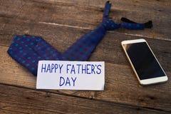 Inscription heureuse du jour de père avec le téléphone portable et lien sur le bois Image libre de droits