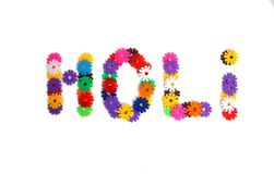 An inscription `HOLI` lined with multi-colored plastic flowers stock image