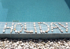 The inscription  holiday  is laid out by pebble on a pool side Stock Photos