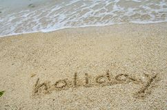 Inscription Holiday on the sand at the beach. Stock Photo