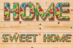 Inscription. Home sweet home from the multi-colored candy sweets on light wooden background Stock Image